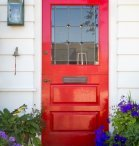 Bright red front door to house with window and mail slot